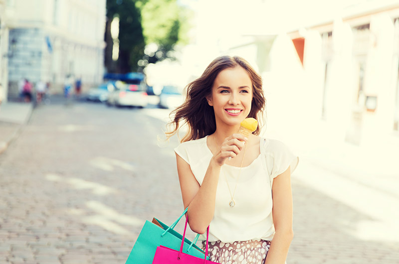 woman with shopping bags and ice cream in city